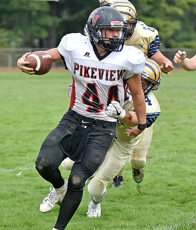 (Brad Davis/The Register-Herald) PikeView's Evan Rose drags Shady Spring defender Justin Black with him for a few yards as the Tiger defense pursues him Saturday afternoon in Shady Spring.