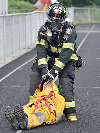 (Brad Davis/The Register-Herald) Mount Hope firefighter Andrew Robinson is timed as he drags a dummy victim from point A to B, one of several segments of an obstacle course designed to test firefighter stamina and endurance during the annual Battle in the Gorge E.M.S. and Fire Competition Sunday morning at Oak Hill High School.