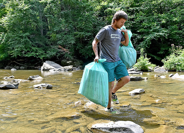 (Brad Davis/The Register-Herald) Volunteer Nathan Sadzewicz hauls garbage pulled from a section of the Peach Tree Creek and falls areas during a cleanup effort Saturday afternoon near Naoma.