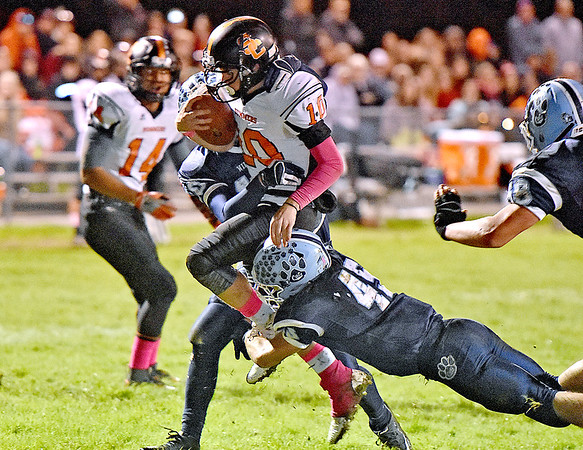 (Brad Davis/The Register-Herald) Summers County quarterback Timmy Persiani tries to cut through Meadow Bridge defenders Caleb Richmond (#45), and Jared Gladwell Friday night in Meadow Bridge.