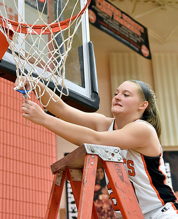 (Brad Davis/The Register-Herald) Summers County senior Tiffani Cline cuts herself off a piece of the net after the Lady Bobcats' Regional Championship victory over Pocahontas County Wednesday night in Hinton.