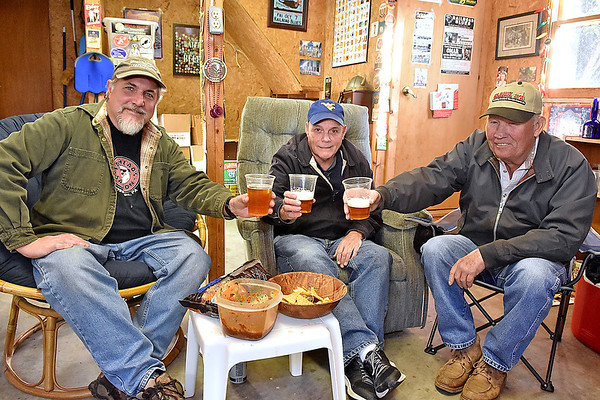 "(Brad Davis/The Register-Herald) Home brewers (from left) Dave Bieri, Wayne Baker and James Bogle offer cheers to the camera as they pose for a quick photo Sunday afternoon in Bieri's garage, where they and others have begun gathering to brew, share recipes and try new takes on existing ones as part of a ""Craft Beer Club"" of sorts."