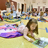 (Brad Davis/The Register-Herald) Crescent Elementary School student Elizabeth Sullivan reads to herself during the school's Read-a-Thon fundraiser Wednesday afternoon. The event was a different take on fundraising where every child got sponsors and collected donations in the hopes of raising a combined $5,000 towards playground equipment and other support items. Participating students then gathered Wednesday in the gym with a pillow and blanket to cozy up with as they read and were read to by their teachers.