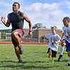 (Brad Davis/The Register-Herald) Young football players Jacob Buckland (2nd from right), 7, and Kingston Clark (far right), 9, try to mimick the technique of fromer Woodrow Wilson player and current Marshall University linebacker Chase Hancock, left, as they work through warm-up drills during the first ever Flying Eagles Fundamentals Camp Saturday Morning at Van Meter Stadium.