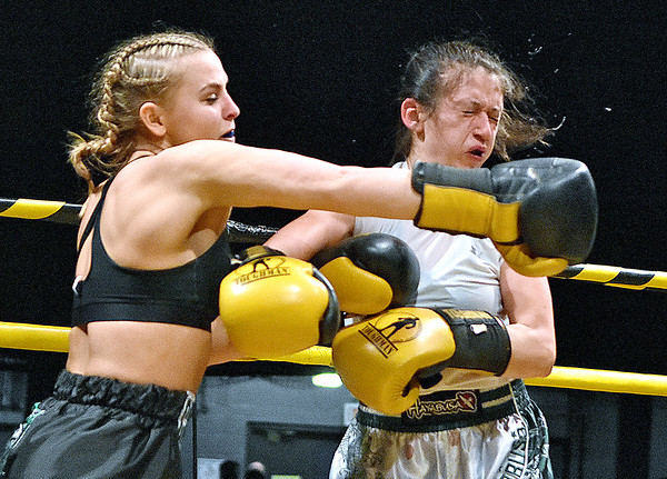 "(Brad Davis/The Register-Herald) Abby Campbell, left, lands a devastating right on opponent Emma Van Scoy during their match in the ""Original"" Toughman Contest Saturday night at the Beckley-Raleigh County Convention Center."