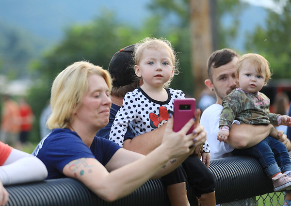 Carmalena Harville talks to someone on the phone with her daughter, Autumn Proctor, 2, as they cheer on their side Valley at their home game against Fayetteville on Friday. (Chris Jackson/The Register-Herald)