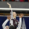 (Brad Davis/The Register-Herald) Woodrow Wilson's Emily Martin spikes the ball as University's Kaliegh Brooks tries to block during State Volleyball Tournament action Friday evening at the Charleston Civic Center.