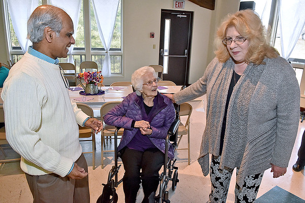 (Brad Davis/The Register-Herald) Ghent resident Florence Mandakunis, middle, is greeted by friends and fellow church members Kim and Bose Mikkilineni during the opening moments of her 100th birthday party Saturday afternoon at Calvary Assembly of God.