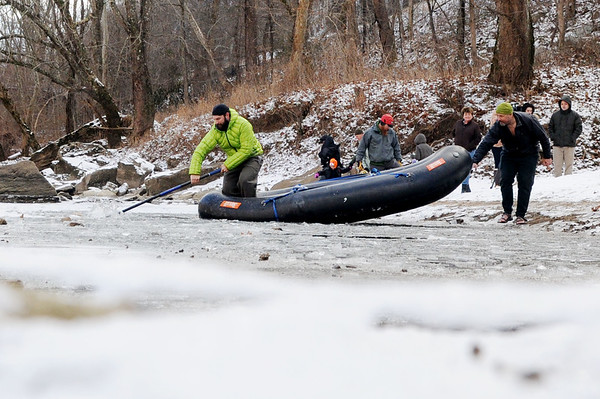 Brad Scott, from Fayetteville, who has participated in five New Year's Day Polar Plunges, works to break ice along the New River in order for participants to run into the ice cold water during the annual plunge Monday in Fayetteville. (Chris Jackson/The Register-Herald)
