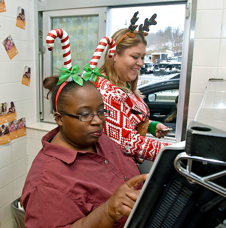 (Brad Davis/The Register-Herald) Festive Beaver McDonald's employees Nikita Lilly, right, and Shannon Nathan work their shift in the drive-through window decked out in holiday garb Wednesday afternoon.