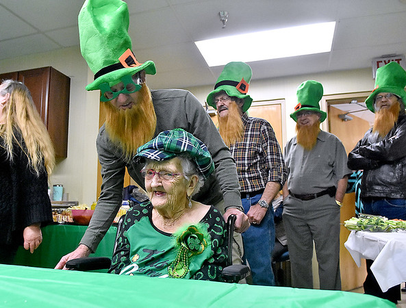 (Brad Davis/The Register-Herald) 100-year-old Shirley Testement is brought into the room by sons (from left) John, Chester, Rick and David Testement during the opening moments of her birthday party Saturday afternoon at Pine Lodge Nursing Home. The proud centurian boasts 10 children (one deceased), 27 grandchildren (one deceased), 44 great grandchildren and 19 great great grandchildren, according to the family.