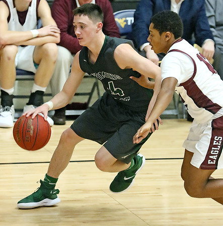 (Brad Davis/The Register-Herald) Wyoming East's Caden Lookabill moves the ball up the court as he's pressured by Woodrow Wilson's Bryant Jones during the Little General Battle for the Armory Tournament Friday night at Beckley-Raleigh County Convention Center.