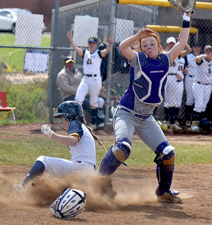 (Brad Davis/The Register-Herald) WVU Tech's Olivia Morey slides home as the throw to the plate sails over the head of Cincinnati Christian catcher Isabella Manuel during the second game of a doubleheader Saturday afternoon at Woodrow Wilson High School.