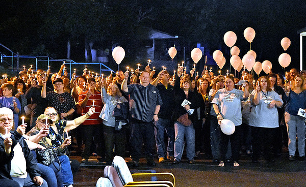 (Brad Davis/The Register-Herald) Friends, family and colleagues of Dr. Luke McElwain light candles and sing songs of remembrance during a heavily attended community vigil Wednesday night at the Webster County Memorial Hospital.