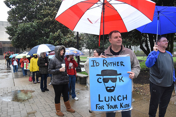 Will Lawerence, cook Ruffmen Elementary School in Charleston, holding sign, waits in line with teachers and other service personnel school workers preparing for a rally at the State Capitol in Charleston during Day 6 of the teachers walkout.<br /> (Rick Barbero/The Register-Herald)