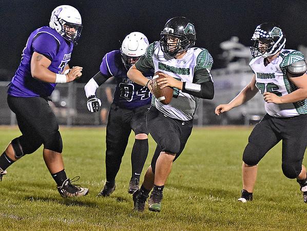 (Brad Davis/The Register-Herald) Wyoming East quarterback Seth Ross is flushed from the pocket by James Monroe defender Luke Wilson, left, Friday night in Lindside.