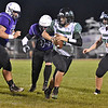 (Brad Davis/The Register-Herald) Wyoming East quarterback Seth Ross is flushed from the pocket by James Monroe defender Luke Wilson, left, Friday night in Lindside.