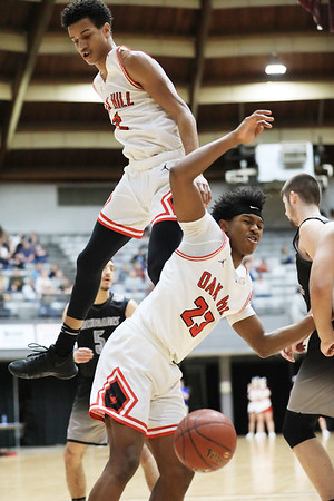 Oak Hill's Michael Beasley (2) and Andrew Work (23) collide after going for an offensive rebound during the first half of their basketball sectional championship against Westside Thursday in Beckley. (Chris Jackson/The Register-Herald)