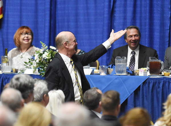 Charlie Houck gestures to Dale Wolfley during the 98th annual Beckley-Raleigh County Chamber of Commerce Annual Dinner at the convention center in Beckley Friday.(Chris Jackson/The Register-Herald)