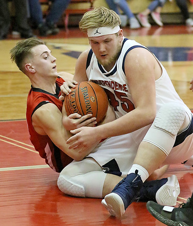 (Brad Davis/The Register-Herald) Independence's Billy Dillinger scrums for a loose ball with Liberty's Ethan Hill Friday night in Coal City.