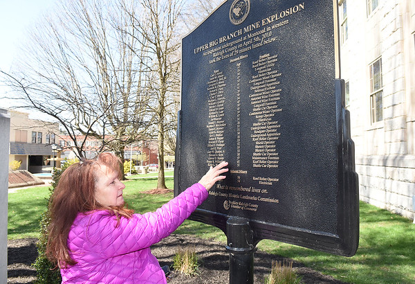 Judy Walls, of Stephenson, places her hand on the name of her brother, Benny Willingham, one of the 29  men who died in the UBB 2010 explosion during a wreath laying ceremony held in front of the Raleigh County Courthouse on Main Street in Beckley<br /> (Rick Barbero/The Register-Herald)