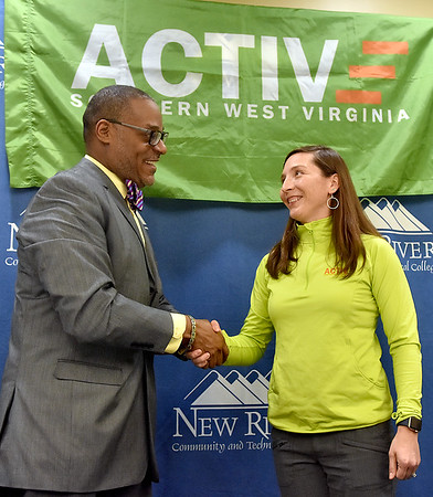 (Brad Davis/The Register-Herald) New River Community and Technical College President L. Marshall Washington and Active Southern West Virginia Executive Director Melanie Seiler shake hands after officially putting their signatures to an agreement between the two Wednesday afternoon.