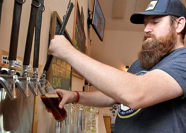"""(Brad Davis/The Register-Herald) Weathered Ground employee Zach Lilly pours a glass of """"AJ's Festbier,"""" brewed specially for the event, during the Cool Ridge brewery's 2nd annual Ocktoberfest Saturday afternoon."""