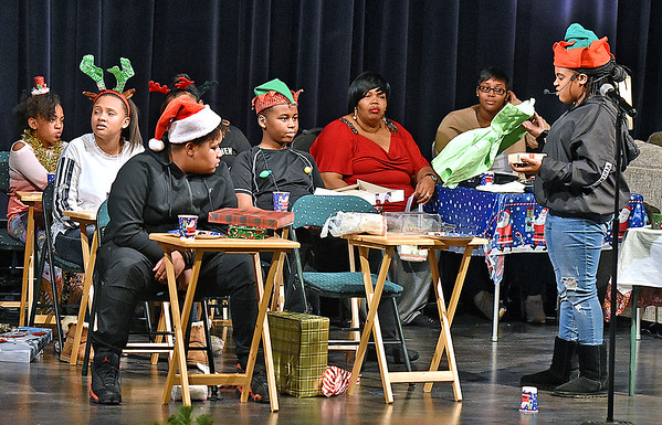 """(Brad Davis/The Register-Herald) Stunned classmates look on as an unappreciative Ebony Scrooge (far right), played by Nia Moore, hurls insults at fellow classmate Jarod (middle, staring forward), played by Drahcir Eneje, who drew her name for their Secret Santa gift exchange and got her a gift not up to the spoiled child's standards in a scene from How Great Thou Art Theater Group's Ebony Scrooge Saturday evening at Tamarack. The play, themed around the classic """"A Christmas Carol,"""" follows the story of Ebony, a teen consumed with materialism and greed who has forgotten the true meaning of Christmas, if she ever knew it at all. The play runs two more showings today at 3:00 and 6:00 p.m."""
