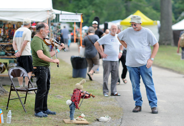"""Lee Mysliwiec, from Bloomington, Ind., plays fiddle with his puppets, """"Harry the Haire"""" and LeRoy the Wonder Dog"""" , to passer-bus during the 2018 Appalachain String Band Festival in Clifftop on Wednesday. (Chris Jackson/The Register-Herald)"""