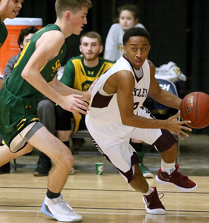 (Brad Davis/The Register-Herald) Woodrow Wilson's Josiah Walton cuts around Greenbrier East defender Cory Beswick Saturday night at the Beckley-Raleigh County Convention Center.