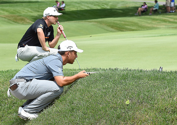 Austin Cook, left and Xander Schauffele looks over their putts on the par 4, 7th hole during the first round of, A Military Tribute at The Greenbrier golf tournament.<br /> (Rick Barbero/The Register-Herald)