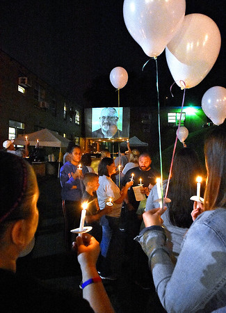 (Brad Davis/The Register-Herald) Friends, family and colleagues of Dr. Luke McElwain light candles and sing songs of remembrance as photos of him stream on a projector screen behind them during a heavily attended community vigil Wednesday night at the Webster County Memorial Hospital.