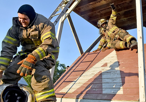 (Brad Davis/The Register-Herald) A Ronceverte firefighter fumbles his helmet as his squadmate follows him over a barrier during the obstacle course portion of the Alderson Fireman's Rodeo Friday evening, part of the town's annual 4th of July Celebration.