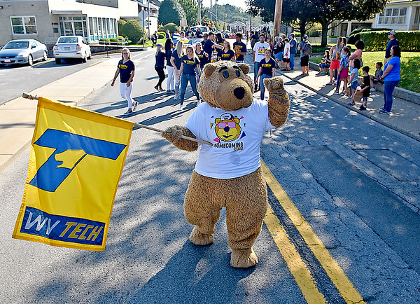 (Brad Davis/The Register-Herald) Monty, the WVU Tech mascot, waves to youngsters in the crowd as he leads the cheerleading squad during the school's homecoming parade Saturday morning in Beckley.