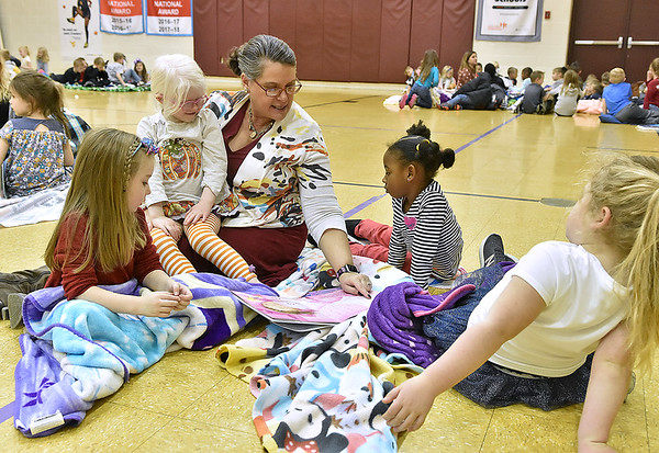(Brad Davis/The Register-Herald) Crescent Elementary School Principal Theresa Lewis reads to young students (from left) Coralee Thomas, Chole Cooper, Neri Schofield and Harper Adkins during the school's Read-a-Thon fundraiser Wednesday afternoon. The event was a different take on fundraising where every child got sponsors and collected donations in the hopes of raising a combined $5,000 towards playground equipment and other support items. Participating students then gathered Wednesday in the gym with a pillow and blanket to cozy up with as they read and were read to by their teachers.