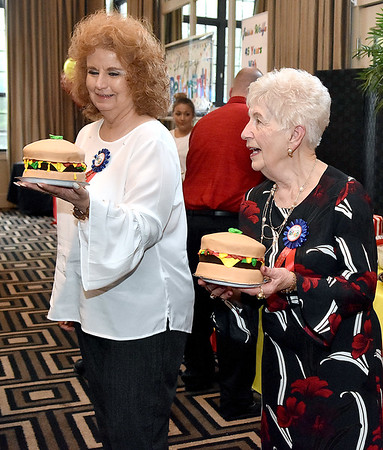(Brad Davis/The Register-Herald) Longtime, retiring Plaza McDonald's employees Jessie Wolfe (45 years), right, and Mary Garris (40 years), each receive one of the two massive, hamburger cake toppers at the conclusion of their retirement party September 19 at Black Knight.