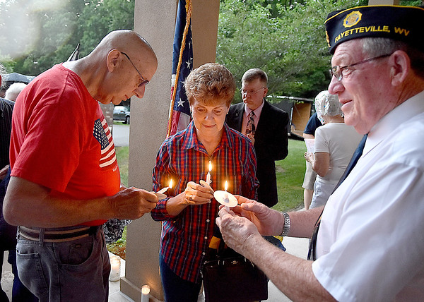 (Brad Davis/The Register-Herald) Fayetteville residents Marilyn and Dale Payne, left, light their candles with help from Mayor Dennis Hanson, a member of American Legion Post 149, during the closing moments of a Memorial Day Community Candlelight Vigil Sunday night at Huse Memorial Park and Mausoleum.