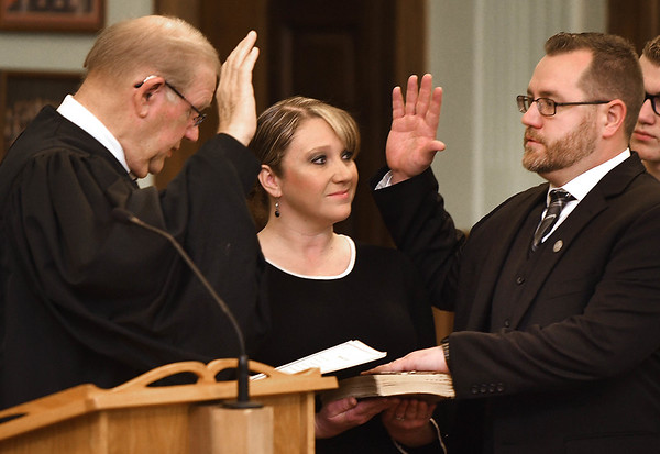Fayette County circuit court judge Paul Blake, left, swears in Thomas H. Ewing, third from left, as the new Fayette County judge appointed by Governor Jim Justice, Ewing replaced John W Hatcher Jr. who recently retired. Standing with Ewing is his wife, Lauri Ewing holding the bible.<br /> (Rick Barbero/The Register-Herald)