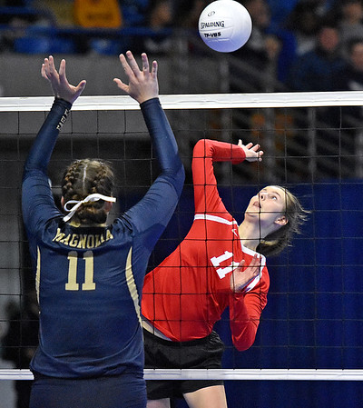 (Brad Davis/The Register-Herald) Greater Beckley Christian's Courtney Green hits the ball as Magnolia's Madelyn Winters defends during State Volleyball Tournament action Friday evening at the Charleston Civic Center.