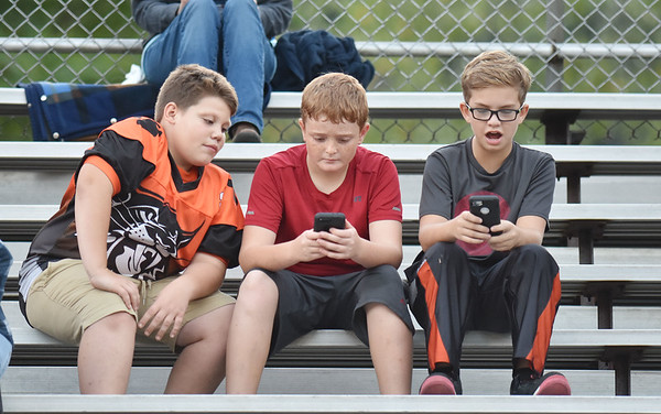 Three youths play on their smartphones prior to Summers County's football game against Mount View Thursday in Hinton. (Chris Jackson/The Register-Herald)