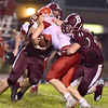 (Brad Davis/The Register-Herald) Parkersburg ball carrier Tyler Moler is taken down by Woodrow defenders Colton Wright, left, and Nicholas Wickline Friday night in Beckley.