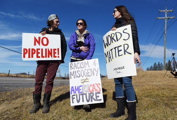 """Taylor Feury, from left, from Lewisburg, Blayne Knapp, and Marian Gheissari, both students at the West Virginia School of Osteopathic Medicine, hold signs during the Protest, March & Rally, hosted by Greater Greenbrier Valley Indivisible and Women's March, at the entrance of the Lewisburg Airport waiting the arrival of the Republican members of congress for their retreat at The Greenbrier Resort Wednesday in Lewisburg. """"We felt like it is the least we could do,"""" said Gheissari,  """"and show President Trump that just because he is in West Virginia he isn't welcome here."""" (Chris Jackson/The Register-Herald)"""