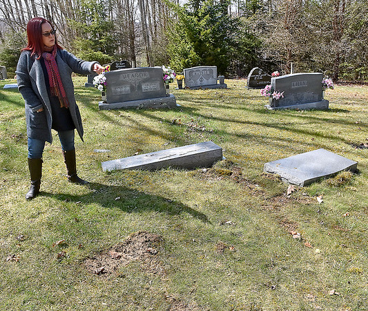 (Brad Davis/The Register-Herald) Ghent resident Patti Morum shows where the broken and displaced monuments marking the graves of her parents Lacy and Beth Meador should be standing inside the Meador family cemetery Sunday afternoon.