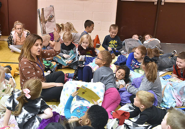 (Brad Davis/The Register-Herald) Teacher Wendy Sullivan reads to a gaggle of cozied-up Crescent Elementary School students during the school's Read-a-Thon fundraiser Wednesday afternoon. The event was a different take on fundraising where every child got sponsors and collected donations in the hopes of raising a combined $5,000 towards playground equipment and other support items. Participating students then gathered Wednesday in the gym with a pillow and blanket to cozy up with as they read and were read to by their teachers.