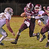 (Brad Davis/The Register-Herald) Woodrow Wilson's Micah Hancock drags George Washington defender Angel Lobato with him as he braces for a hit from Isaac Isabell (#12) Friday night in Beckley.
