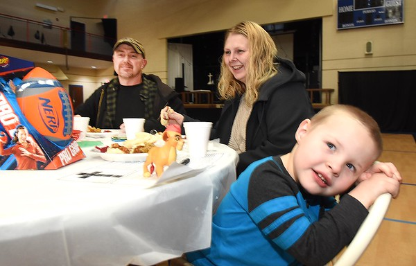 Michael  Williams, left, Carrie Wade and her son Josiah Wade, of Oak Hill eating lunch during the Community Christmas Dinner held at The Place in Beckley Monday afternoon.<br /> (Rick Barbero/The Register-Herald)