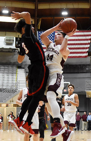 Woodrow Wilson's Bryce Radford (14) goes up over St. Albans Rodney Toler (3) during the first quarter of their basketball game Monday in Beckley. (Chris Jackson/The Register-Herald)