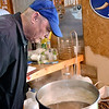 (Brad Davis/The Register-Herald) Home brew enthusiast Wayne Baker takes in the aroma of a brewing batch of friend Dave Bieri's I.P.A. style creation Sunday afternoon at Bieri's house.