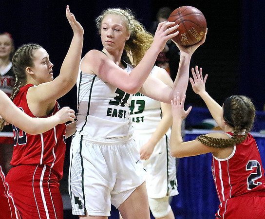 (Brad Davis/The Register-Herald) Wyoming East's Emily Saunders looks for an open teammate as Wayne defenders Sara Hooks, left, and Lakyn Adkins converge on her Friday morning at the Charleston Civic Center.