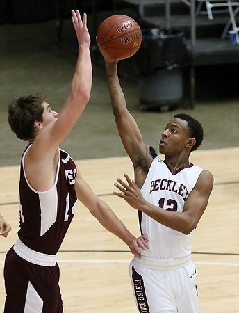 (Brad Davis/The Register-Herald) Woodrow Wilson's Tyriek Walton drives as Virginia Episcopal's Patrick Kelley defends during the Little General Battle for the Armory Tournament Friday night at the Beckley-Raleigh County Convention Center.